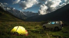 Camp at night with car. Camp at night with car in a mountain range at moon night. Illuminated tent, moonlight. Peacks with snow. 4K timelapse stock video