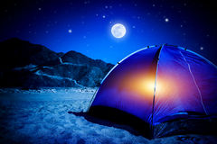 Camp at night. Camp on sandy beach, tent at the night with light inside, moon light, active tourism, hiking and traveling concept stock photo