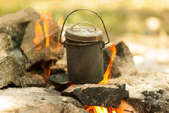 Camp pot is on the fire. Marching smoked pot boiling on the fire on the stones. Pot of cylindrical form with lid. Main color: orange, beige, black Stock Image