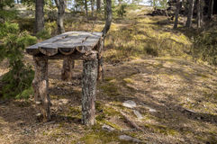 Camp on the rocky shore of the lake. Old wooden table of pine tr Stock Photos