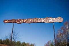 Camp sign in German. A sign saying Camp Site, in German. Clear blue sky, some trees Royalty Free Stock Photos