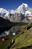 Camp site 3. Two tents set against a mountainous view in the Peruvian countryside. Green grass and a clear lake also visible royalty free stock image