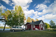 Camp site house and car. A scenic Swedish camp site with a wooden red painted house (hut,cabin) and cars parked nearby Stock Photo
