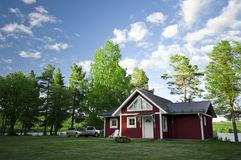 Camp site house and cars. A scenic Swedish camp site with a wooden red painted house (hut,cabin) and cars parked nearby Royalty Free Stock Photography
