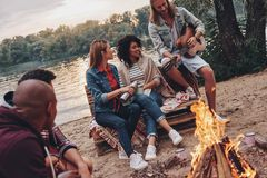 Camp songs. Group of young people in casual wear smiling while enjoying beach party near the campfire stock photo