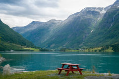Camp table on the fjord shore, Norway. Wooden barbecue furniture on the shore of Oldevatnet fjord, Norway. Evening light landscape Royalty Free Stock Photography