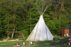 Camp with teepee. Modern teepee replica made of canvas with playground in camp in front of forest royalty free stock images
