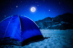 Camp tent on the beach at night. Full moon glowing in dark night, summer adventure and active lifestyle concept Royalty Free Stock Photo