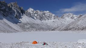 Camp Tent Snowfall Frozen Lake Himalayas Mountains Panorama Travel Tourism 4k. Concept of tourism and travel: multicolored tents on the shore of the frozen Gokyo stock video