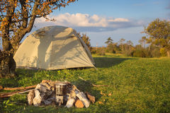Camp tent stands in the meadow near bonfire site with pot on it Stock Photos