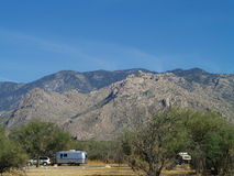 Camp trailer at campground. A view of a travel trailer parked at an Arizona desert campground with the Catalina Mountains, in the background Stock Image
