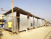Camp. Zinc sheets are made into box shape worker  camp  on the cement floor near construction site and a yellow T-shirt in the front on a sunny day with blue sky Stock Photography