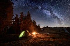 Campa för natt Upplyst tält och lägereld nära skog under natthimmel mycket av stjärnor och den mjölkaktiga vägen royaltyfri foto