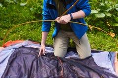 Campa i tältet - turisten som ställer in ett tält på campa Slutet upp händer för man` s rymmer ett tält, medan ställa in - upp et Royaltyfri Fotografi