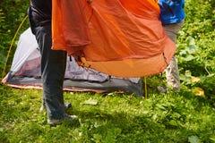 Campa i tältet - turisten som ställer in ett tält på campa Två män ställde in ett tält i det härliga stället i skogen Royaltyfri Foto