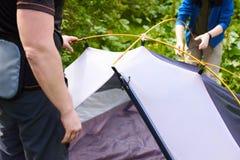 Campa i tältet - turister som ställer in ett tält på campa Slutet upp händer för man` s rymmer ett tält, medan ställa in - upp et Royaltyfri Fotografi