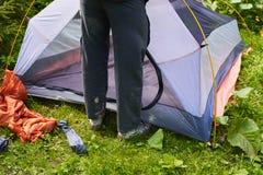 Campa i tältet - turister som ställer in ett tält på campa Slutet upp händer för man` s rymmer ett tält, medan ställa in - upp et Royaltyfri Bild