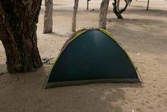 Campa lopptillbehör: Tält på sandstranden i sommartid royaltyfri bild