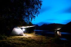 Campa med ett upplyst tält på stranden och fjorden i bergen av Norge under natt med en molnig blå himmel och stjärnor royaltyfria bilder