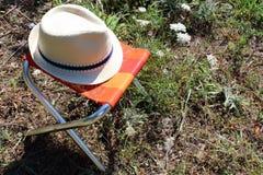 Campa stol och hatt i fältet royaltyfria foton