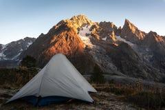 Campa tält framme av glaciären fotografering för bildbyråer