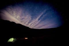 Campa under stjärnor i berg Arkivbild