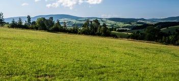 Campagna della montagna con i prati, i campi, i villaggi, gli alberi, le colline ed il cielo blu con le nuvole Immagine Stock Libera da Diritti
