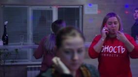 Campagne bij een partij Iedereen is bezig met zijn zaken Vrienden Het meisje in geroepen rood Zij nam de telefoon op en stock videobeelden