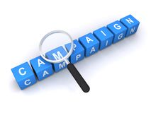 Campaign. Letter blocks forming the word campaign with a magnifying glass focusing on it Royalty Free Stock Images