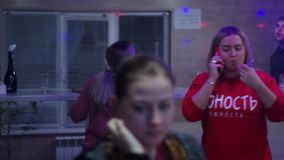 Campaign at a party. Everyone is busy with his business. Friends. The girl in red called. She picked up the phone and stock video footage