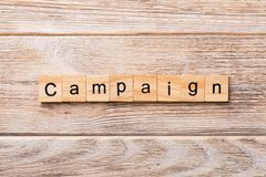 CAMPAIGN word written on wood block. CAMPAIGN text on wooden table for your desing, concept stock photography