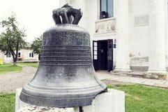 Campana antigua puesta en pedestal delante de la iglesia del molde de Cuza Imagenes de archivo