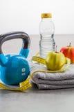 Campana, cinta métrica, manzanas y agua de la caldera para la atención sanitaria del ajuste Imágenes de archivo libres de regalías