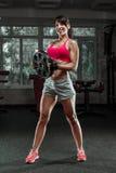 Campana d'oscillazione del bollitore della donna di forma fisica alla palestra Fotografie Stock