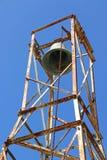 Campana de iglesia y campanario oxidado en un fondo del cielo azul Fotografía de archivo