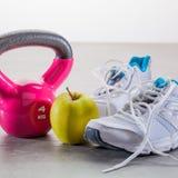 Campana de la caldera con las zapatillas de deporte y manzana sana sobre piso del gimnasio Imagen de archivo libre de regalías