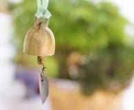 Campana de oro con el fondo verde del bokah Imagen de archivo libre de regalías