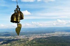 Campana de oro dos delante de la montaña y del cielo azul imagen de archivo libre de regalías