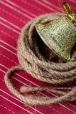 Campana de oro en un fondo rojo Fotografía de archivo libre de regalías