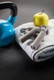 Campana del ejercicio y de la dieta, de la manzana y de la caldera en la estera del gimnasio Foto de archivo libre de regalías
