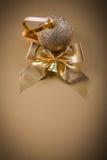 Campana dell'arco della palla di Natale su fondo dorato Immagini Stock