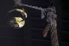 Campana di desiderio dorata del tempio giapponese tradizionale sulla corda con la riflessione brillante fotografia stock