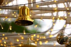 Campana di Natale dorata e piccole luci immagini stock libere da diritti