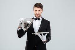 Campana di vetro di sollevamento del metallo del giovane cameriere felice dal vassoio del servizio Fotografie Stock
