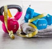 Campana, pesas de gimnasia, cinta métrica y agua de la caldera en el gimnasio Imagen de archivo