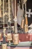 Campanaccii dell'ottone e del metallo che appendono in una stalla medievale Fotografia Stock