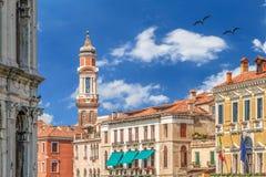 Campanario de los apóstoles de los santos con el reloj viejo en Venecia - Italia con el cielo azul colorido y las nubes blancas Foto de archivo