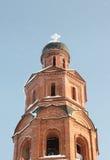 Campanario del ladrillo con la cruz nevada en las nevadas Fotografía de archivo