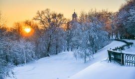 Campanario del monasterio y del bosque nevoso en la puesta del sol fotografía de archivo