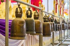 Campanas de cobre amarillo budistas en Wat Rai Khing Fotos de archivo